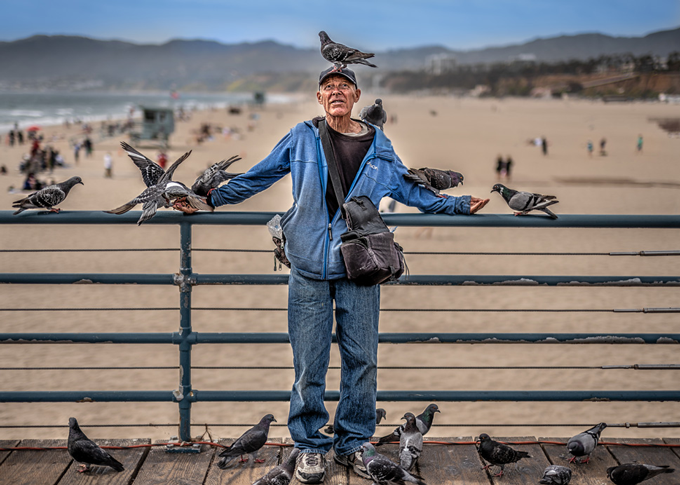 Image taken by Michael Schoenfeld of man at beach surrounded by pigeons