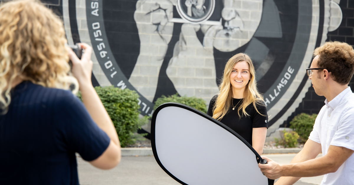 photographer using assistant to hold reflector for light on model