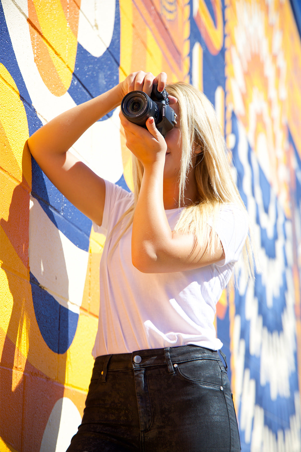 girl using Canon eos rebel SL3 with colorful wall behind her