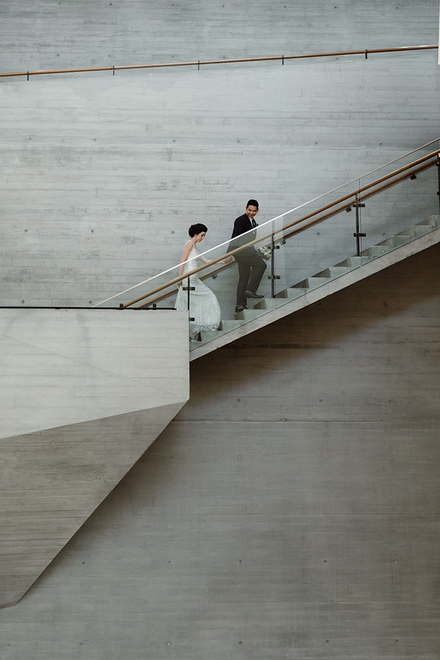 Chelsea Fabrizio photography image of bride and groom walking up stairs in large building