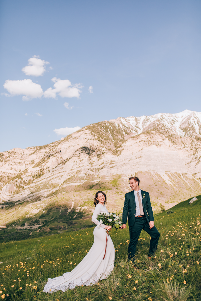 julia mathers photo of couple in wedding attire on hill