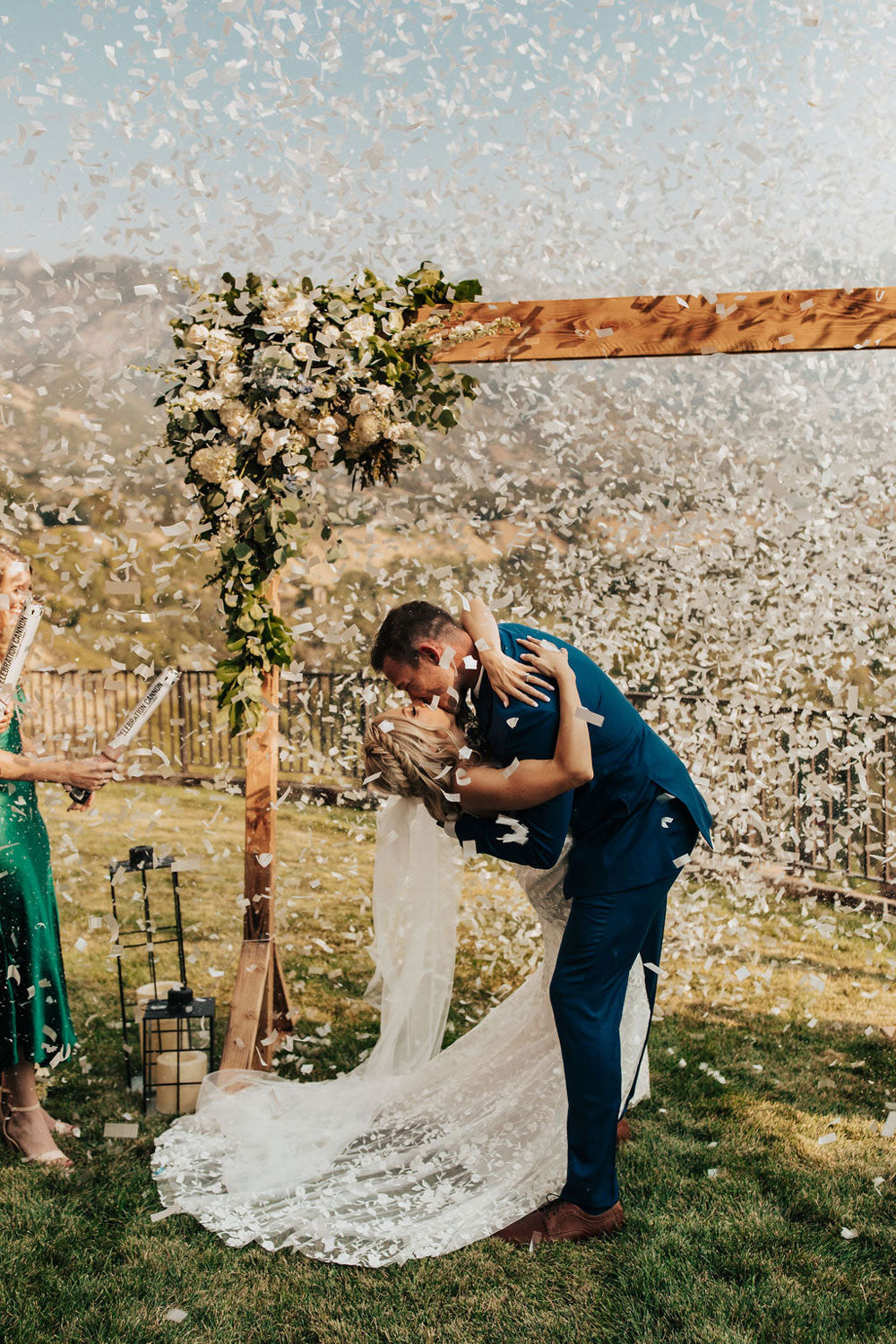 wedding with groom and bride kissing with confetti