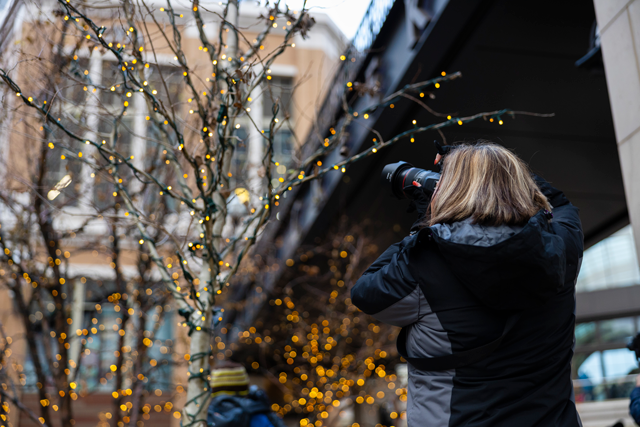 Photographer capturing the lights in the trees outside city creek