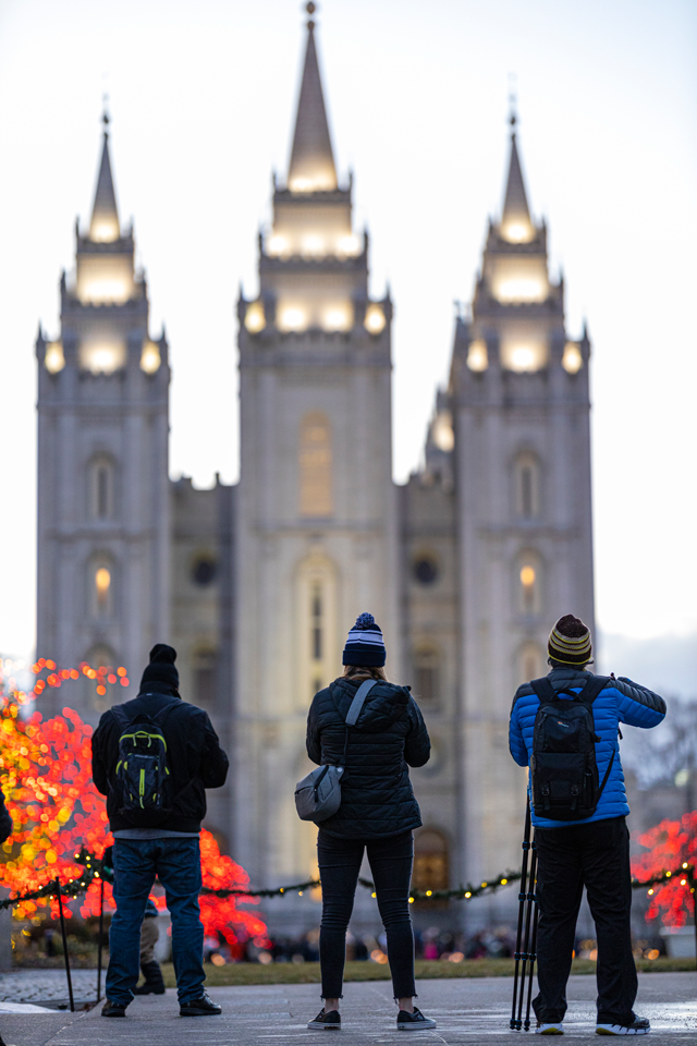 three people getting ready to take photos of the salt lake city temple and temple lights