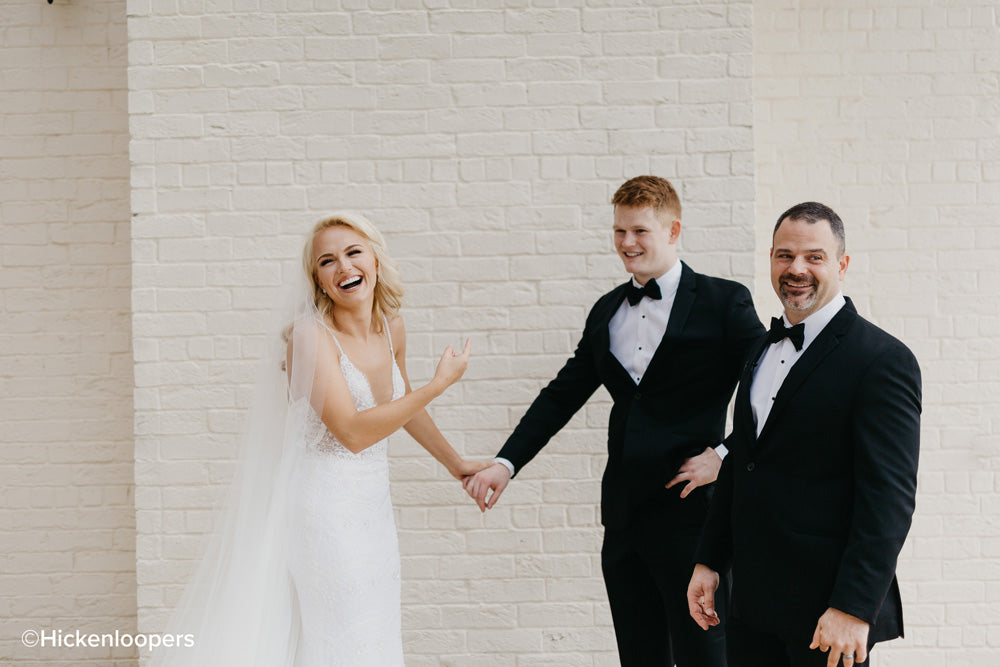 bride with family with white brick background by scott hickenlooper