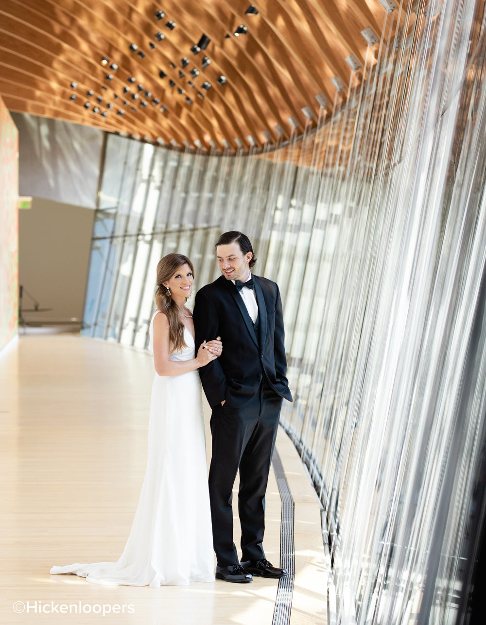 bride and groom in building surrounded by glass paneling by scott hickenlooper