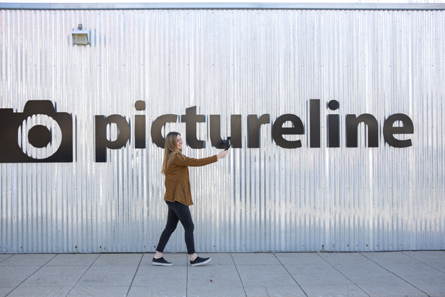 vlogger using a tripod grip to take video in front of pictureline sign