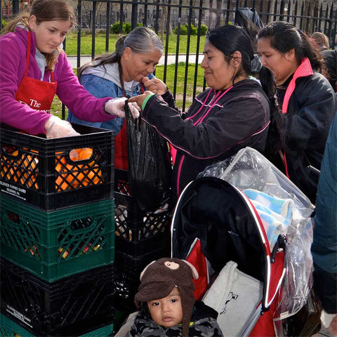 Family receiving grocery bag at the Mission's outreach program