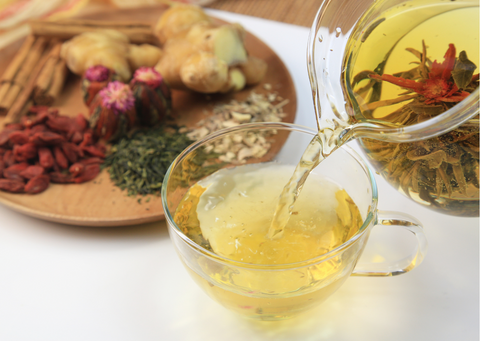 pouring herbal tea into a cup