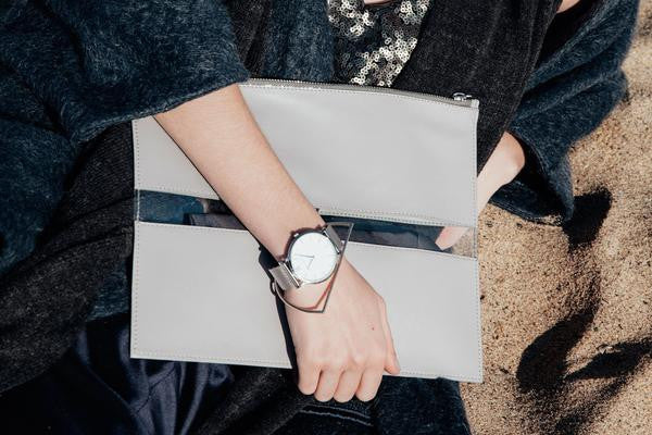 Lifestyle photo of Death in Paris Rivage Concrete grey lamb nappa leather and clear pvc stripe clutch bag