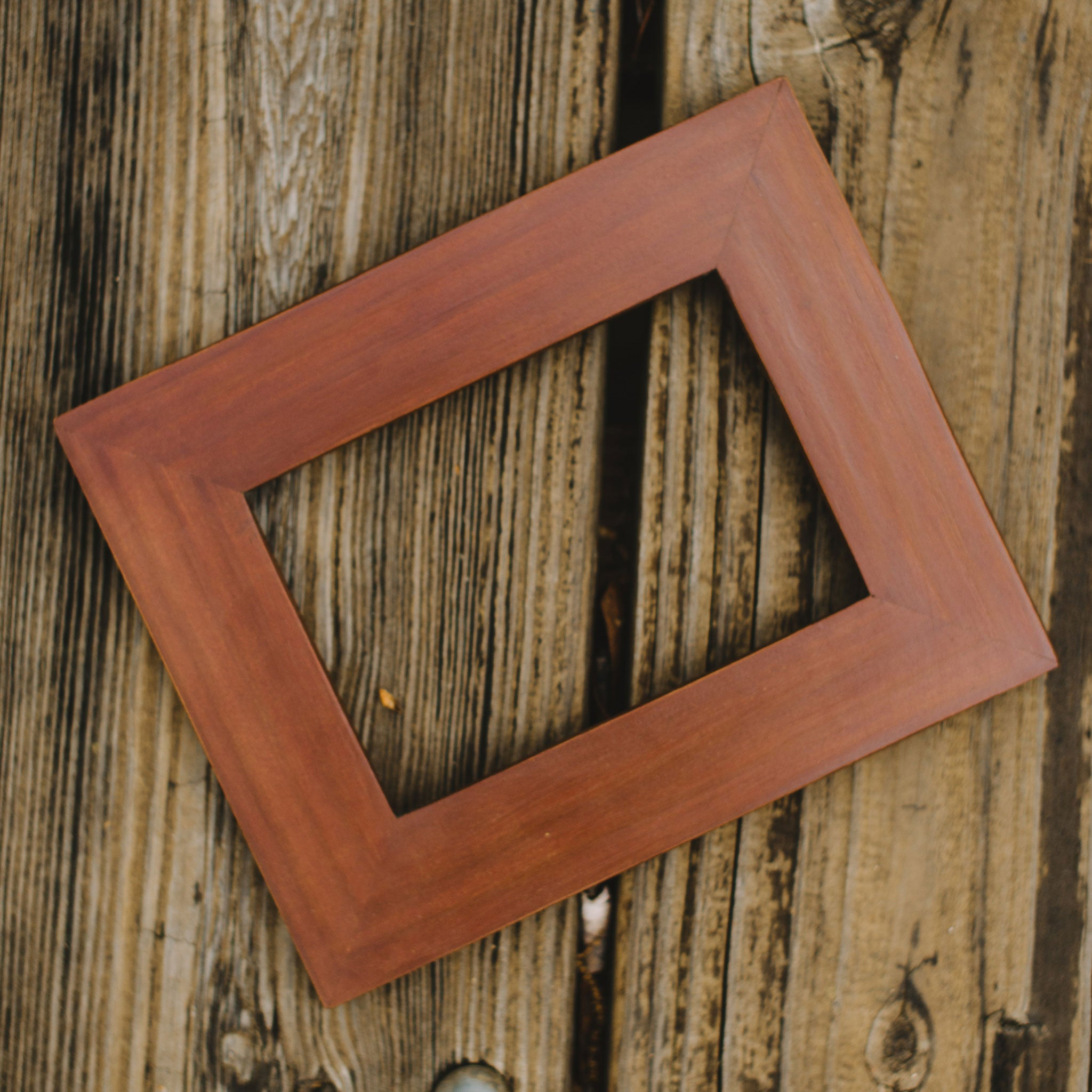 this solid wood picture frame is hand shaped from a plank and topped off with