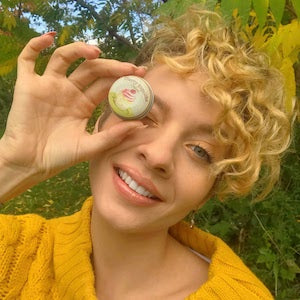 Beautiful smiling woman holding a lip balm tin in front of her right eye.