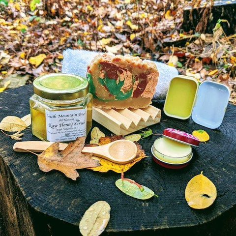 The Nature Walk gift set is inspired by the beauty of the fall. It contains a rosemary soap, scented with essential oil, and decorated with mineral mica and volcanic clay forming swirls in ochre, red, green and beige. The beech wood soap dish will help extend the life of your soap by allowing it to dry between uses. The thick and soft washcloth will intensify the creamy lather leaving your skin moisturized. The honey and vitamin E scrub will gently remove dead cells and leave your skin revitalized. The bamboo spoon will allow you to scoop out as much as you need. The beeswax lip balm will restore your lips after being outdoors, and the dandelion infused salve will soothe your dry hands after the fall gardening and wilderness adventures.