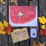 Bird nest on twig cards, botanical soap, and soothing salve lay flat on a weathered table with red and yellow fall leaves around them.