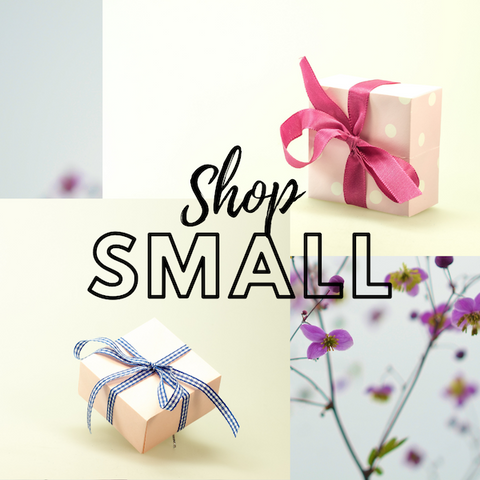 Shop Small reads in the middle of an image with two gift boxes over a background of ethereal purple flowers.
