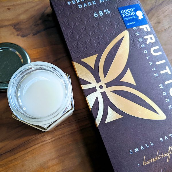 Dark milk Fruition chocolate with an open jar of creamed honey on an olive tree wood board