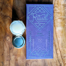 Dark Ritual chocolate bar with an open jar of creamed raw honey on an olive tree wood board