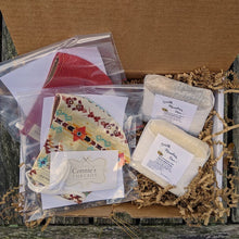 Two handmade face masks by Connie's Threads and two natural gentle soaps by South Mountain bees in a cardboard gift box with kraft crinkle paper.