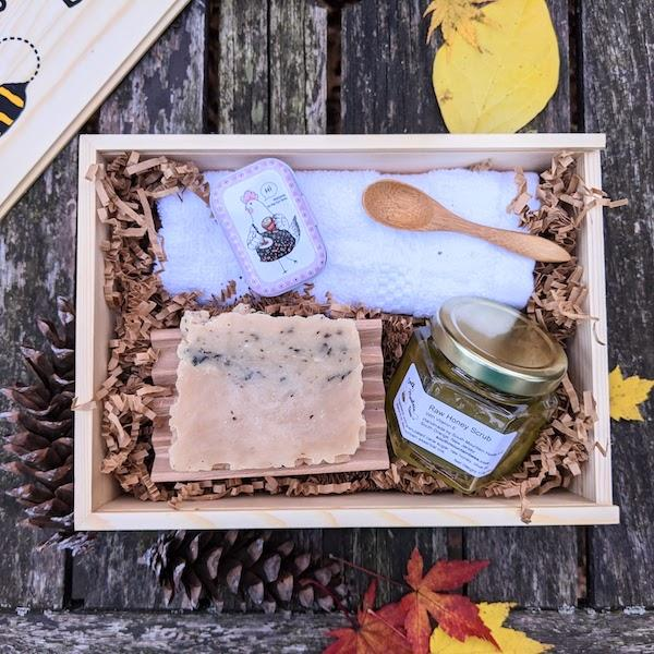 The Pampering Gift Box has a raw honey scrub with bonus bamboo spoon, a natural honey soap, a soothing salve with dandelion infused oils, a beech wood soap dish, and a hotel grade 100% cotton washcloth. It all comes in the most charming, reusable sliding top wooden box.