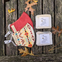 Two handmade colorful 100% cotton face masks and two natural gentle soaps on an aged wooden table with dry fall leaves.
