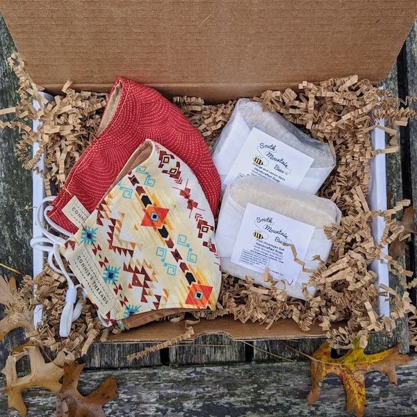 Two lovely colorful 100% cotton face masks and two natural gentle soaps in a cardboard gift box with kraft crinkle paper