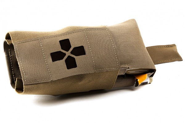 The carrier slides into the outer pouch. Trauma supplies are accessed by pulling the contents from either side.