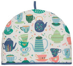 Tea Cosy with design of teapots and cups and saucers of different colors and styles. Predominant colors are pale pink, dark and light blue, and dark and light green against white background, with dark blue trim.
