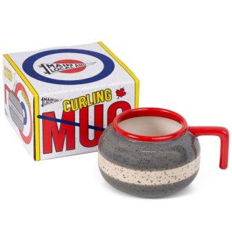 Novelty mug made to look like curling rock, grey with red trim and handle and white stripe, in front of box with primary colors design.