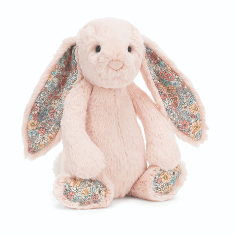 Sitting plush bunny with long ears. Pale pink fur, floral lining of ears and foot pads.