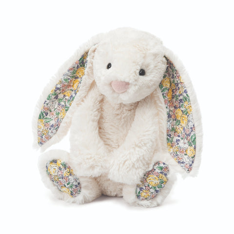 Sitting plush bunny with long ears. Cream colored fur, floral ear linings and foot pads.