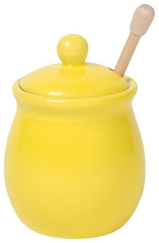 Bright yellow glazed stoneware honeypot with birch dipper.