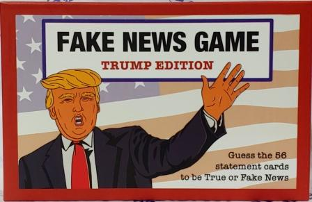 "Cover of ""Fake News Game Trump Edition"" with cartoon image of Donald Trump in front of American flag. Text at bottom right reads ""Guess the 56 statement cards to be True or Fake News."""