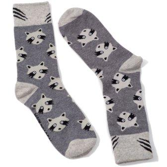 Pair of grey socks with pattern of white and black raccoon faces. White toes, heels and cuffs, with black claw like markings on cuffs.
