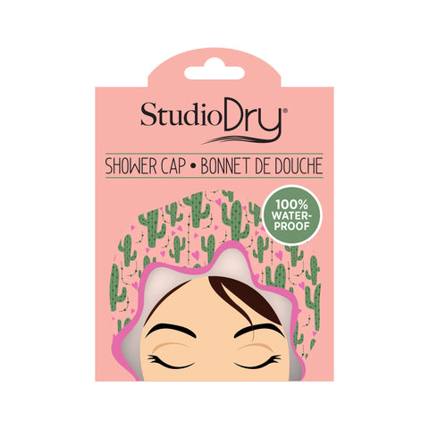 Studio Dry Cactus Shower Cap in package. Cap is pale peach with lavender hearts and trim and green cacti.