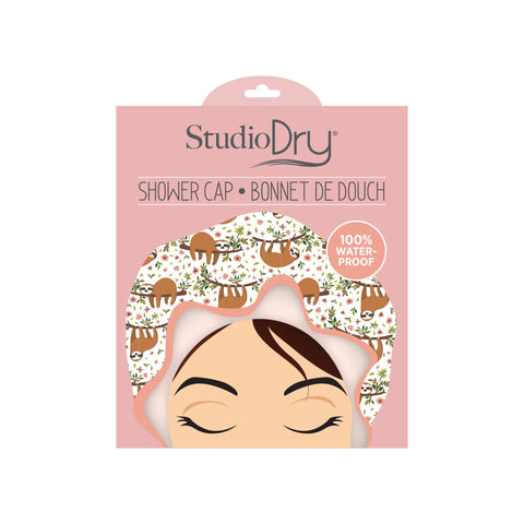 Studio Dry Sloth Shower Cap in package. Cap is white with design of brown sloths on branches and pale peach trim.