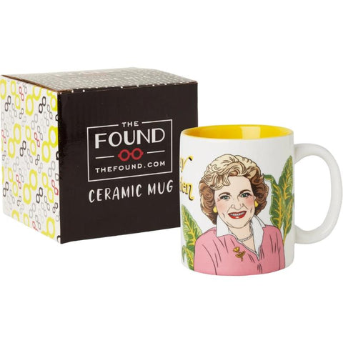 "Mug with illustration of smiling Betty White in front of gift box. Mug color scheme is white, yellow, green, and pink. On the side of the mug opposite the handle the end of the words ""Stay Golden"" in yellow text can be seen."