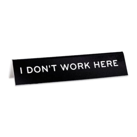 "Black desk sign with white text reading ""I Don't Work Here."""
