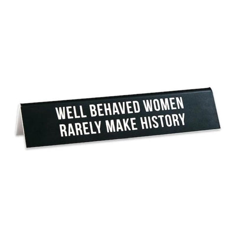 "Black desk sign with white text reading ""Well Behaved Women Rarely Make History."""