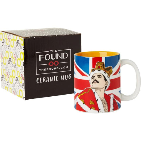 Mug with illustration of Freddie Mercury in royal robe and crown against background of the British flag, in front of gift box.