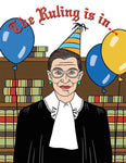 "Front of card with illustration of Ruth Bader Ginsberg in her robe, in front of shelves of law books, wearing a yellow and blue party hat, with yellow and blue balloons on either side of her. Red script at the top of the card reads, ""The Ruling is in...."""