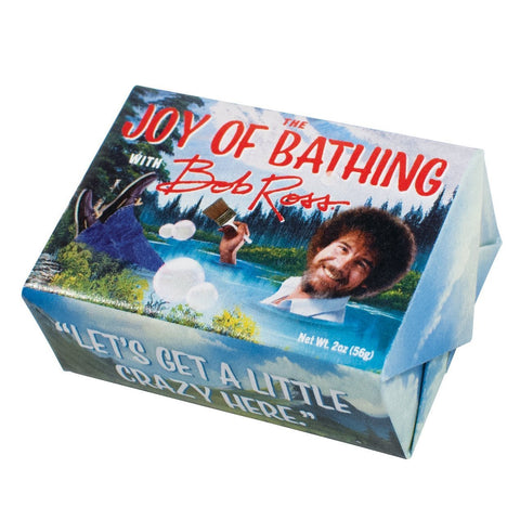 "2 oz bar of Bob Ross soap. Packaging shows a nature scene with fully clothed Bob Ross, holding paint brush, appearing to ""bathe"" in lake. Text on front of bar: ""The Joy of Bathing with Bob Ross."" Quote on bottom of bar: ""Let's Get A Little Crazy Here."""
