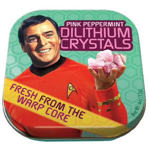 "Lid of mints tin. Scottie holding up pink dilithium crystals and smiling. Mint green honeycomb patterned background. Yellow banner across left bottom corner reads ""Fresh From The Warp Core."" Pink letters at top right read ""Pink Peppermint Dilithium Crystals."""