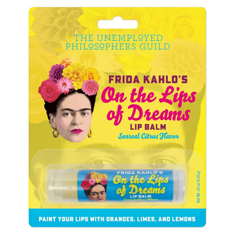 "Yellow and turquoise package containing Frida Kahlo's On the Lips of Dreams Lip Balm, Surreal Citrus Flavor. Text on package is red, pink, turquoise or white. White text against turquoise at bottom of package reads ""Paint Your Lips With Oranges, Limes, and Lemons."" Lip balm tube has turquoise label with white and yellow text. Both package and tube feature same illustration of Frida Kahlo's head crowned with flowers.."