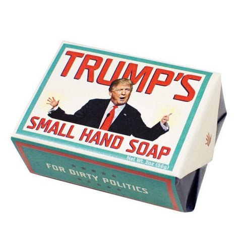 "Bar of Trump's Small Hand Soap in package. Front of package has image of Donald Trump waving comically tiny hands. Red lettering and red tie on Trump. White background and turquoise ""frame"" around image. Bottom of package is turquoise with red ""frame"" around the white text: ""For Dirty Politics."""