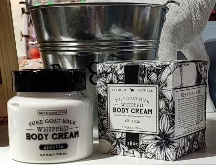 8 oz clear jar of Beekman 1802 Pure Goat Milk Arcadia Whipped Body Cream next to box for same. White cream, black jar lid and text. Box design is black and white with pattern of flowers.