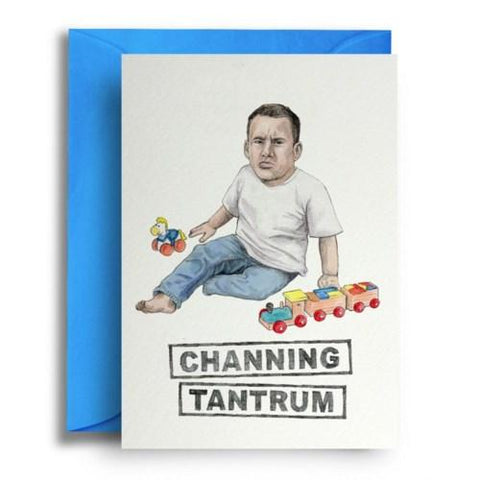 Card on top of sky blue envelope. Card shows illustration of Channing Tatum as a toddler playing with wooden toys and scowling. White background.