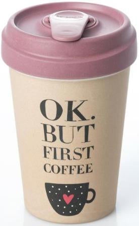 "Travel mug with dark rose lid and cream cup. Black text on cup reads ""OK. But First Coffee,"" above cartoon image of coffee mug with polka dots and red heart."