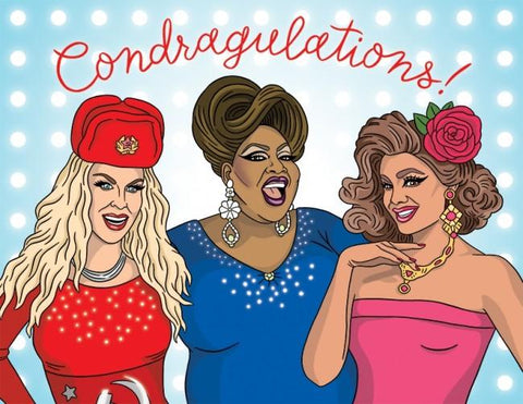 "Front of card features illustration of three glamorous drag queens of different races against pale blue background with white polka dots. Red script over them reads ""Condragulations!"""