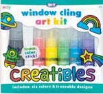 "Creatibles DIY Window Cling Art Kit package with colorful designs of planet, rainbow, shooting star, and a monster that says ""trace, color, stick!"" Shows red, yellow, green, blue, purple, and black paints."