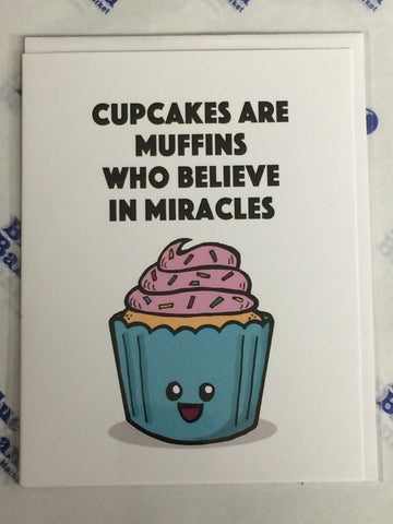 "Front of card with cartoon cupcake with blue liner, pink icing and happy face. White background, black text at top that reads ""Cupcake Are Muffins Who Believe In Miracles."""